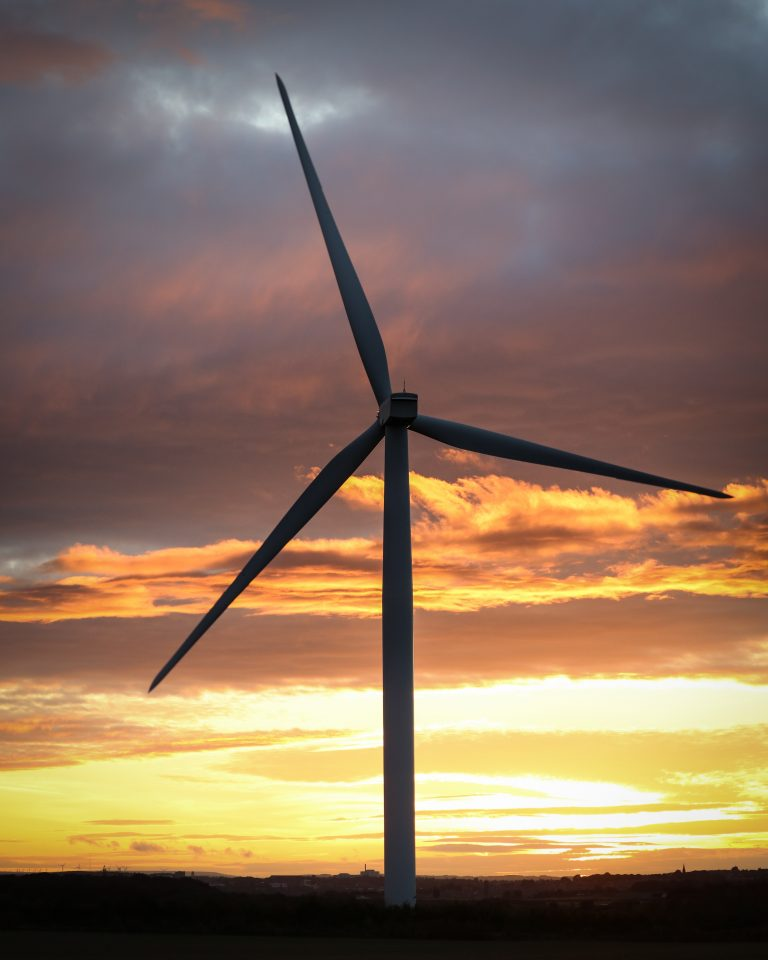 Wind turbine in colorful sky